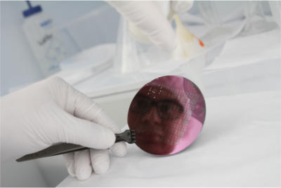 Researcher looking into a small mirror in his lab