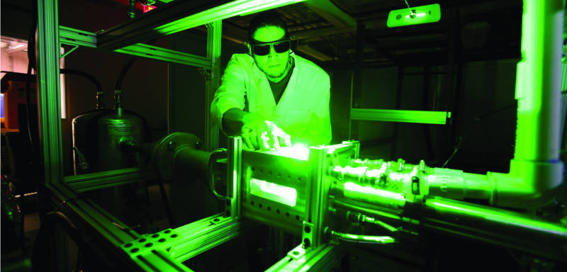 UTEP student working in a lab under a green light